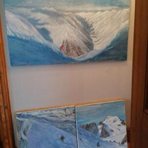 Three oil paintings of skiers in the hallway